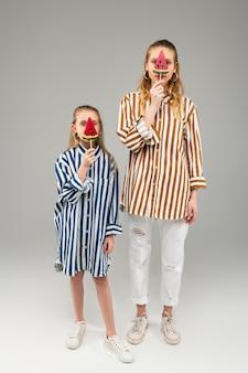 Lindas garotas de cabelos compridos em camisas listradas brilhantes segurando um doce em forma de melancia na altura do rosto