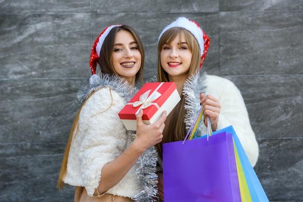 Lindas garotas de papai noel com caixas de presente e guirlanda cintilante comemorando o ano novo