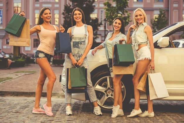 Lindas garotas elegantes estão segurando sacolas de compras.