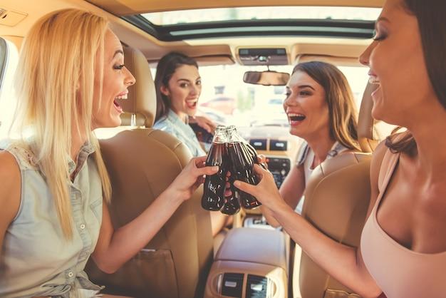 Lindas garotas elegantes estão tocando copos de bebidas
