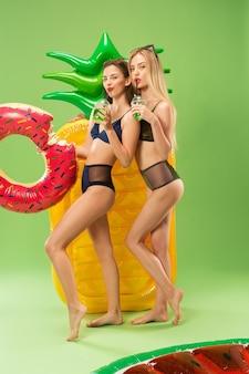 Lindas garotas em maiô posando no estúdio e bebendo suco de laranja. retrato de verão adolescentes caucasianos no verde