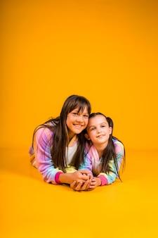 Lindas garotas em pijamas luxuosos deitadas em um fundo amarelo com um lugar para o texto