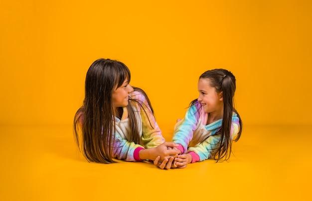 Lindas garotas em pijamas luxuosos se comunicam em um fundo amarelo com um lugar para o texto