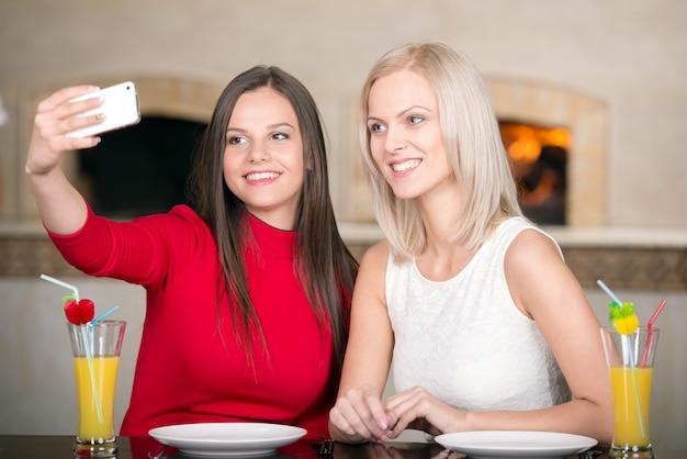 Lindas garotas estão esperando por pizza e tirando foto.