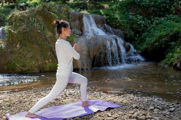 Lindas garotas estão jogando yoga no parque