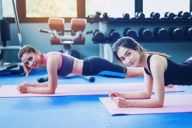 Lindas garotas exercem com yoga no ginásio público