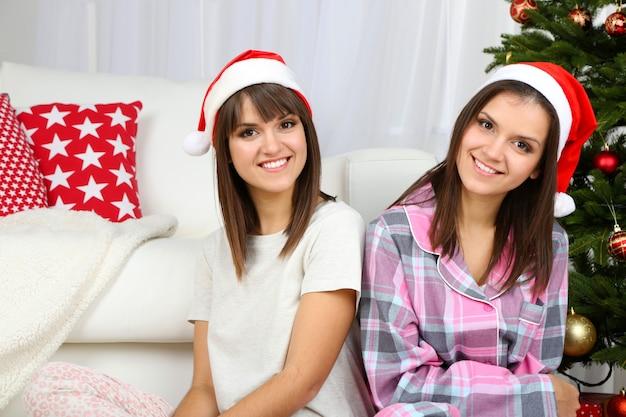 Lindas garotas gêmeas de pijama perto da árvore de natal em casa