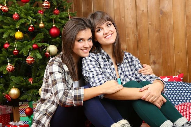 Lindas garotas gêmeas perto da árvore de natal em casa