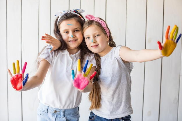 Lindas garotas mostrando suas mãos pintadas em pé contra a parede de madeira branca