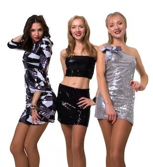Lindas garotas posando no estúdio em branco em vestidos brilhantes - isolado Foto Premium