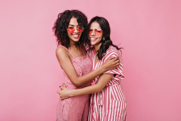 Lindas garotas românticas se abraçam de maneira amigável. senhoras em óculos de sol rosa rindo.