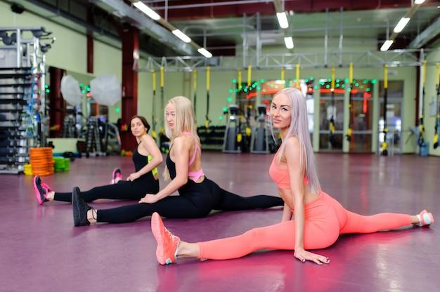 Lindas garotas sentam nas divisões no ginásio