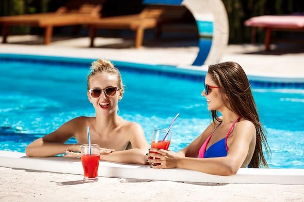 Lindas garotas sorrindo, falando, bebendo cocktails, relaxando na piscina.