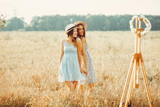 Lindas garotas têm um descanso em um campo