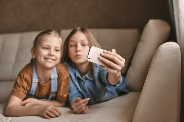 Lindas garotas tiram selfies em seu telefone enquanto estava deitado no sofá. as irmãs fazem uma pausa nos trabalhos de casa e tiram fotos durante a quarentena
