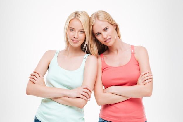 Lindas garotas vestidas com camisetas e jeans posando