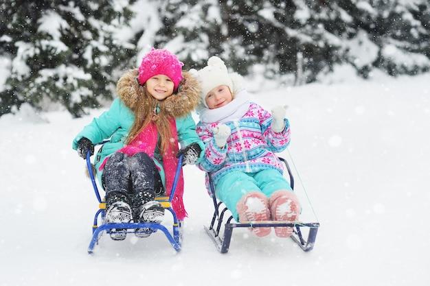 Lindas garotinhas com roupas coloridas de inverno estão andando de trenó