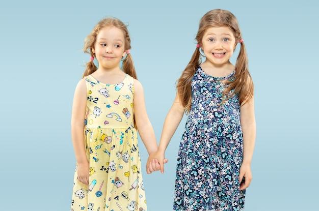 Lindas garotinhas emocionais isoladas no espaço azul. retrato de meio comprimento de irmãs ou amigas felizes usando vestidos e brincando