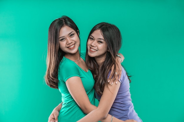 Lindas gêmeas asiáticas se abraçam e sorriem alegremente olhando para a câmera, sobre um fundo verde