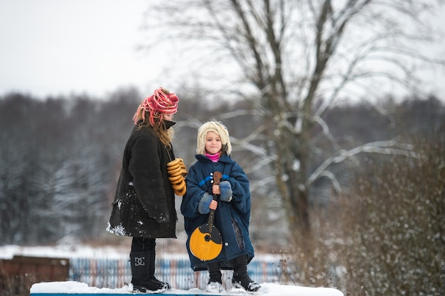 Lindas irmãs da aldeia ficam no banco com balalaica, rolos secos em forma de anel e sorrisos no inverno