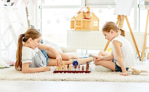 Lindas irmãs jogando xadrez no chão