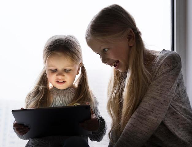 Lindas irmãs usando tecnologia em casa