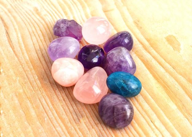 Lindas joias, pedras acrobáticas de ametista, quartzo rosa e apatita. cristais mágicos roxos e rosa em um fundo de madeira.