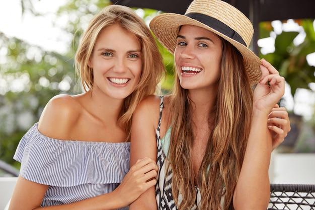 Lindas lésbicas riem e se abraçam enquanto passam bons momentos juntas, sentam-se contra o interior do café ao ar livre, aproveitem o descanso de verão, tenham expressões alegres. homossexualidade e conceito de relacionamentos do mesmo sexo.