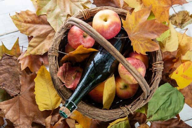 Lindas maçãs e garrafa de cidra, em folhas de outono