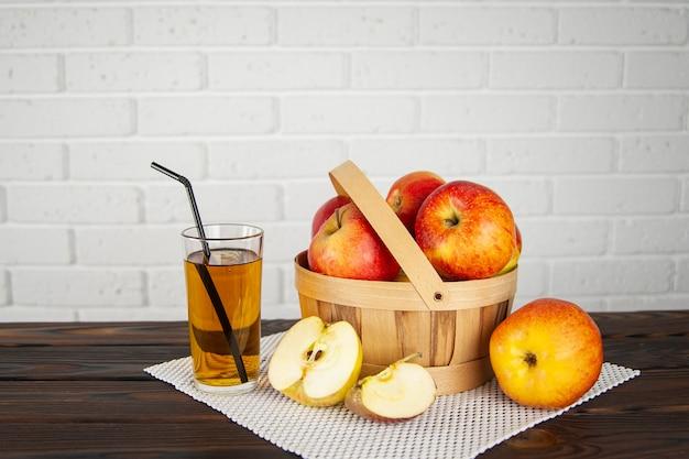 Lindas maçãs em uma cesta de madeira sobre uma superfície de madeira e um copo de suco de maçã