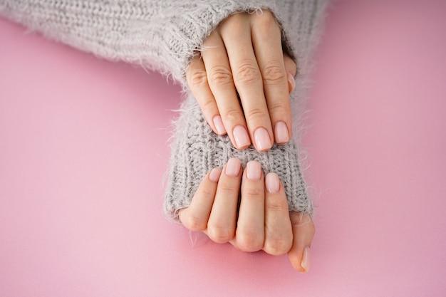 Lindas mãos de uma jovem com bela manicure em um fundo rosa, plana leiga. cuidados com o inverno, pele, conceito de spa.