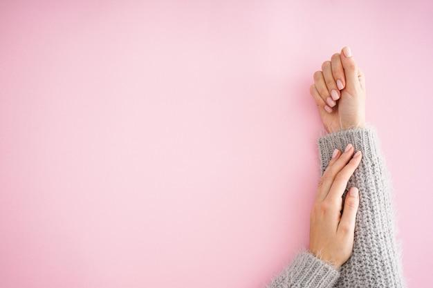 Lindas mãos de uma jovem com bela manicure em um fundo rosa, plana leiga, lugar para texto. cuidados com o inverno, pele, conceito de spa