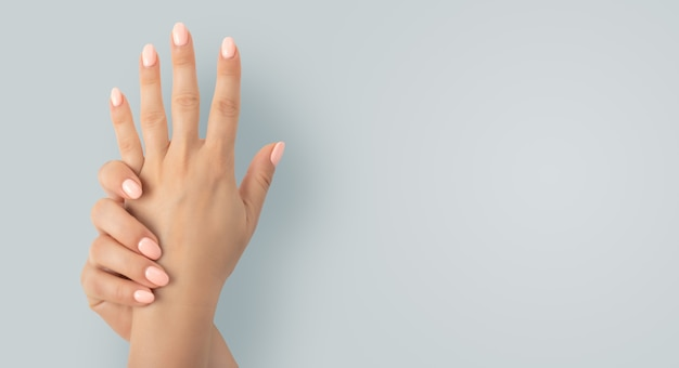 Lindas mãos femininas com esmalte de gel de manicure elegante em fundo cinza. closeup vista de mulher com belas mãos em fundo cinza, espaço para texto. tratamento de spa, manicure