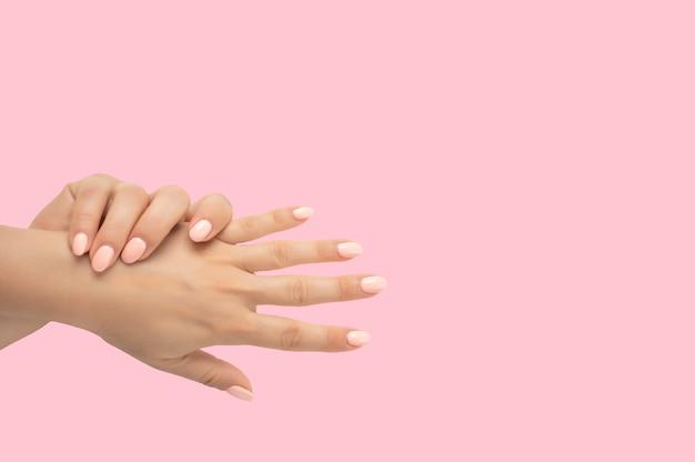 Lindas mãos femininas com esmalte de gel de manicure elegante em fundo rosa. vista superior das mãos femininas preparadas com manicure pastel no fundo rosa. vista do topo. copie o espaço