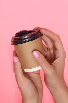 Lindas mãos femininas com esmalte rosa perfeito, segurando a xícara de café de papel na superfície rosa.