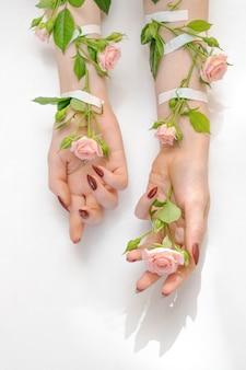 Lindas mãos femininas com flores rosas rosa isoladas