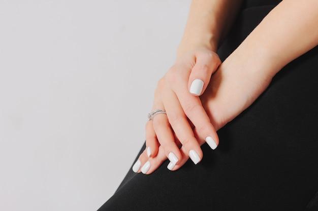 Lindas mãos femininas com manicure branco e anel de noivado,