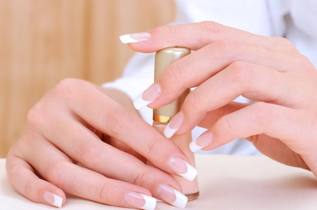 Lindas mãos femininas com manicure francesa de beleza segurando esmalte de garrafa