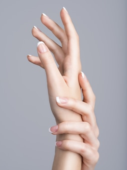 Lindas mãos femininas com manicure francesa nas unhas