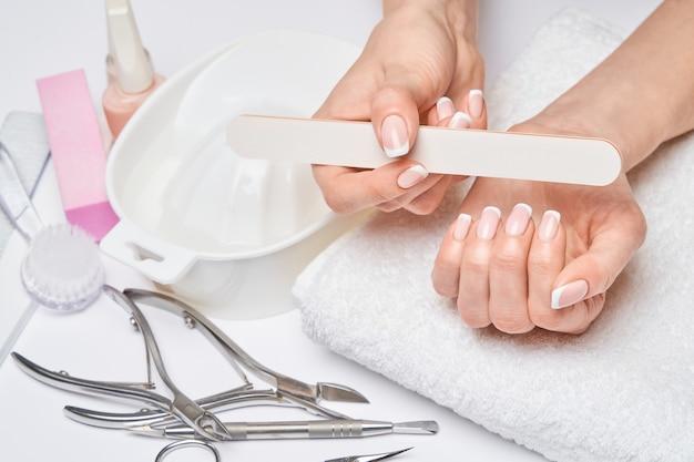 Lindas mãos femininas com manicure francesa sobre fundo cinza claro.