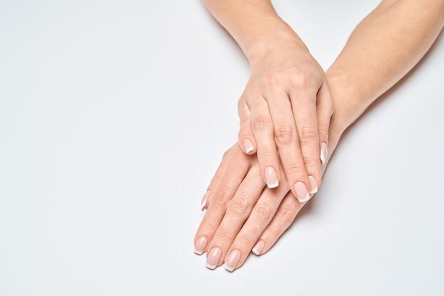 Lindas mãos femininas com manicure francesa sobre superfície cinza claro