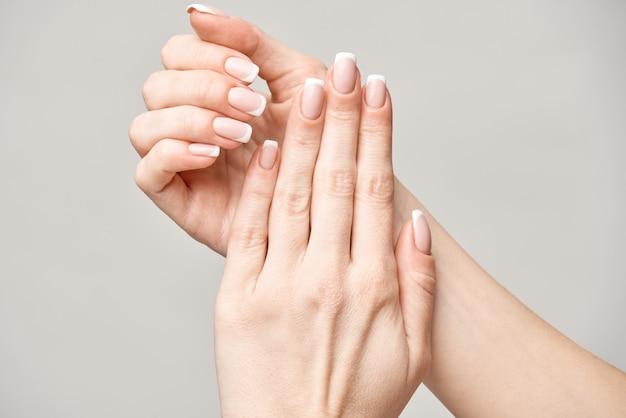 Lindas mãos femininas com manicure francesa