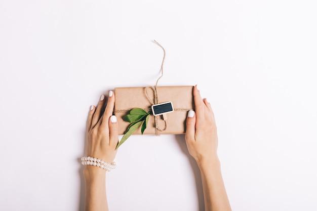 Lindas mãos femininas com manicure segurando uma caixa com um presente na mesa branca