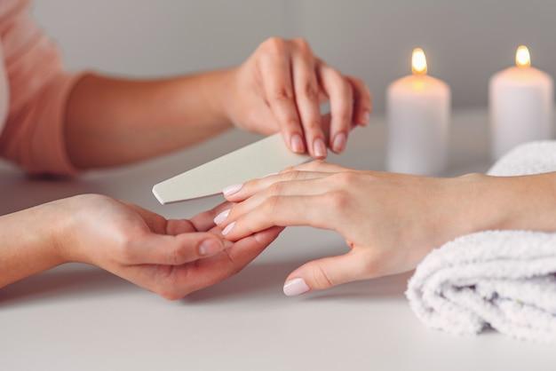 Lindas mãos femininas com manicure spa no salão de beleza. lustra as unhas usando limas.