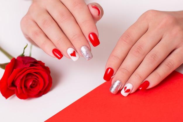 Lindas mãos femininas com românticas unhas de manicure e corações e desenhos para o dia dos namorados