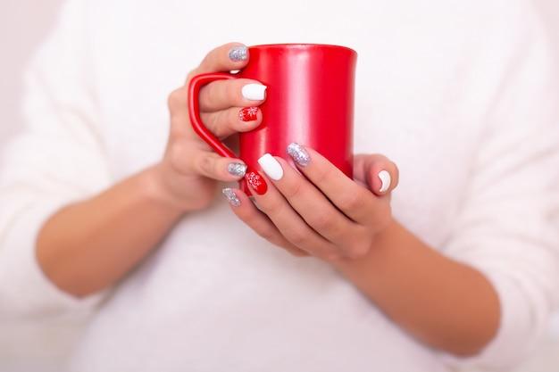 Lindas mãos femininas com unhas de manicure de inverno, segurando um copo vermelho