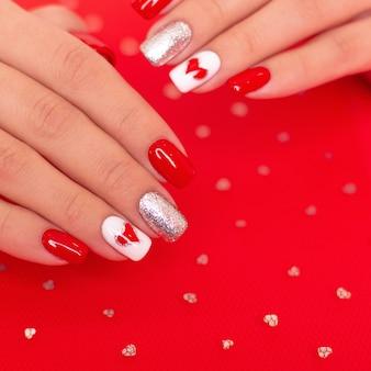 Lindas mãos femininas com unhas vermelhas de manicure, corações e desenho de dia dos namorados