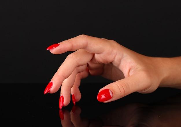 Lindas mãos femininas com unhas vermelhas isoladas em preto