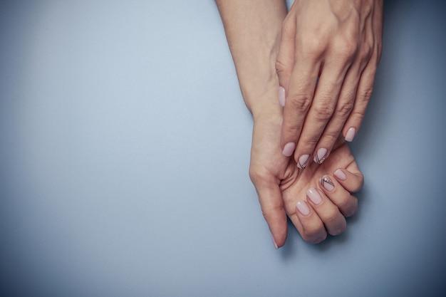 Lindas mãos femininas e uma manicure na moda em azul