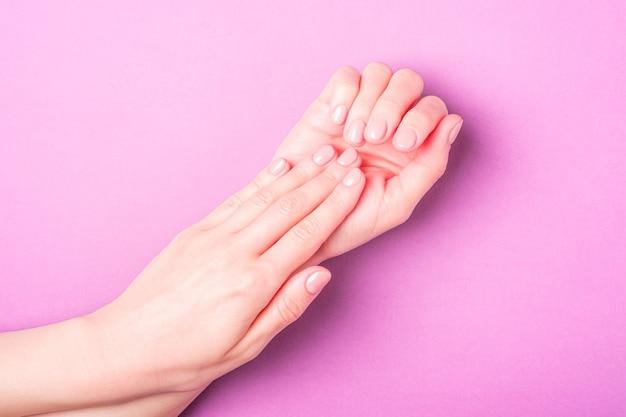 Lindas mãos femininas mostrando conceito fresco de manicure, pele e unhas